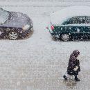 Photographie d'une rue enneigée avec des voitures sous la neige pour illustrer l'article d'Adesa sur l'entretien des pare-brises en hiver.